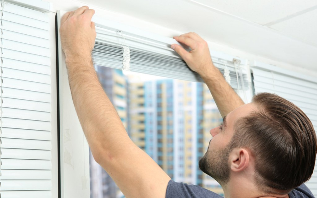 Man mounting the window blinds